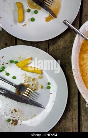 Scatto dall'alto di una piastra a vuoto con gli avanzi di un pasto in un ambiente rustico backround in legno Foto Stock