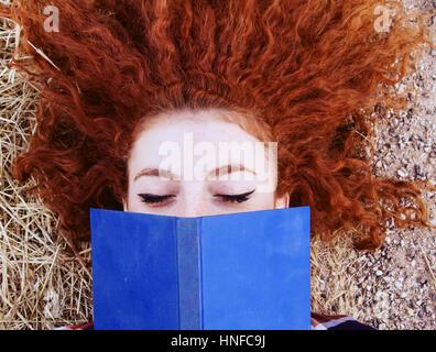 Giovane donna redhead la lettura di un libro Foto Stock