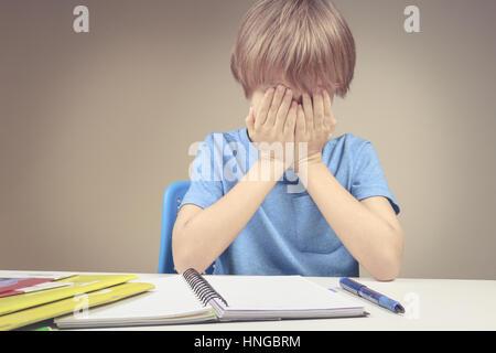Stanco triste bambino facendo i compiti a casa. Il ragazzo stufi e si copre il viso con le mani. Istruzione, scuola, Foto Stock