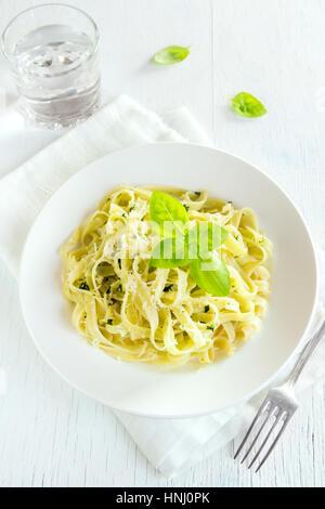 Tagliatelle al pesto, il formaggio e le foglie di basilico sulla piastra bianca - una sana pasta fatta in casa Foto Stock