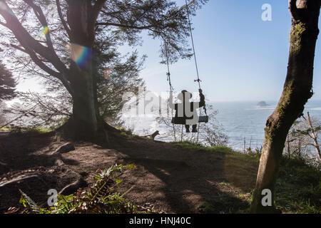 Vista posteriore dell'uomo oscillare mediante una struttura ad albero contro il mare sulla giornata di sole Foto Stock