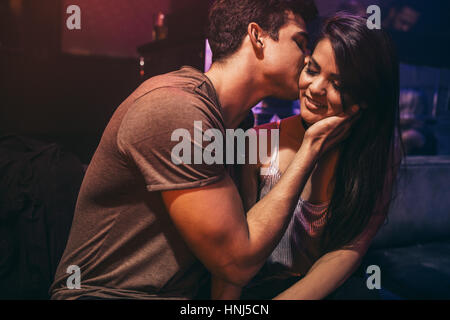 Coppia giovane in amore al night club. Uomo di baciare la sua ragazza seduta al lounge bar. Foto Stock