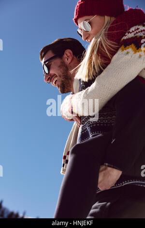 Giovane giocare nella neve. Uomo Donna dando piggyback ride per le vacanze invernali. Foto Stock
