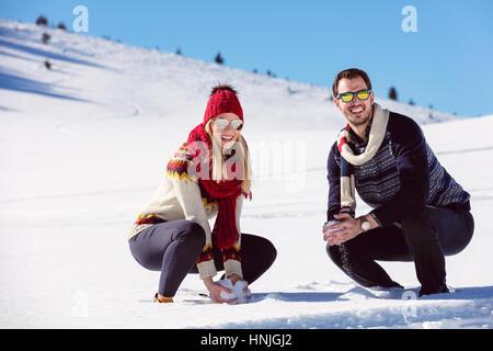 Lotta con le palle di neve. Inverno giovane divertendosi in snow all'esterno. Giovani gioiosi felice multi-razziale Foto Stock