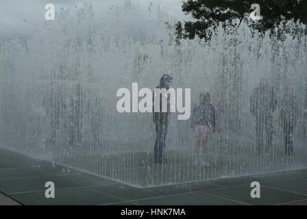 Bambini che giocano tra acqua sprinkler nella Southbank, Londra, Regno Unito. Foto Stock