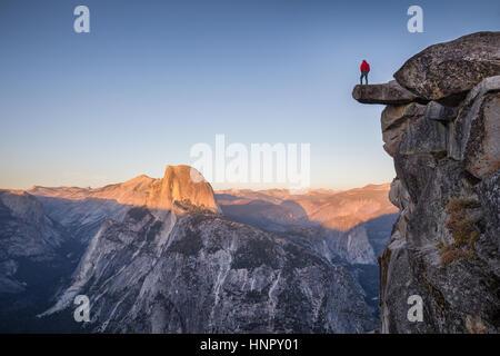 Un maschio di escursionista in piedi su una roccia a strapiombo a Glacier Point godendo la vista mozzafiato verso Foto Stock
