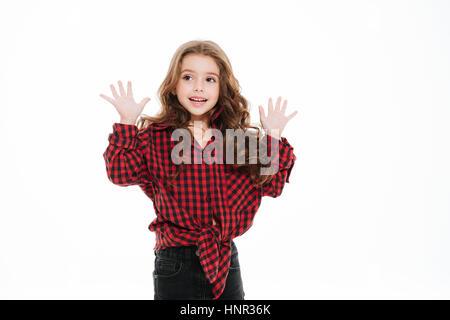 Beautiul sorridente bambina in plaid shirt in piedi con le mani alzate su sfondo bianco Foto Stock