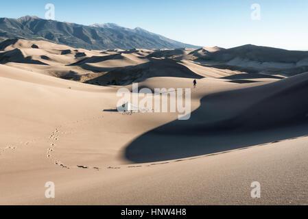 Orme di camper camminare vicino a tenda in dune di sabbia