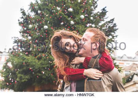 Giovane giocando piggyback davanti dell albero di Natale Foto Stock