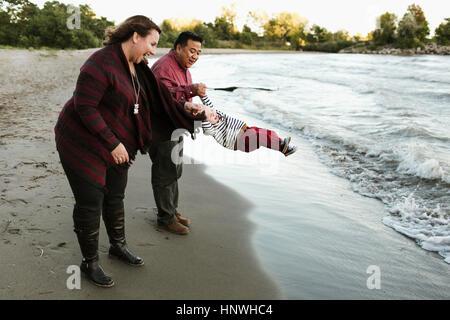 Il padre e la madre sulla spiaggia swinging baby boy, Toronto, Ontario, Canada Foto Stock