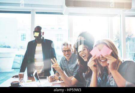 Bella giovani si divertono con sticky notes seduti insieme al tavolo del bar vicino alla finestra luminosa, giocando a nome del gioco Foto Stock