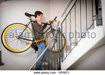 4aca96077eb0d4 Giovane uomo che porta fixie bicicletta su per le scale Hipster Foto Stock