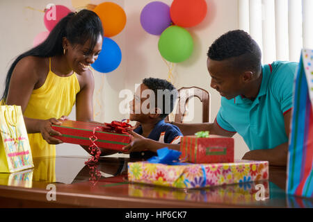 Felice famiglia nero a casa. African American padre, madre e bambino festeggia il compleanno, divertendosi a parte. Foto Stock