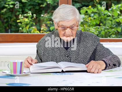 Felice donna anziana la lettura di un libro in camera Foto Stock