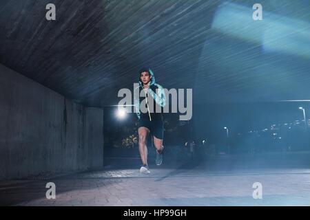 Sano giovane uomo jogging nella città di notte. A piena lunghezza shot dei maschi di atleta che corre sotto il ponte. Foto Stock