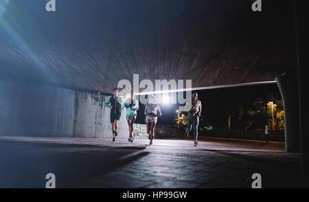 Gruppo di corridori in esecuzione sotto un ponte in città. Giovani uomini e donne jogging insieme a notte. Foto Stock