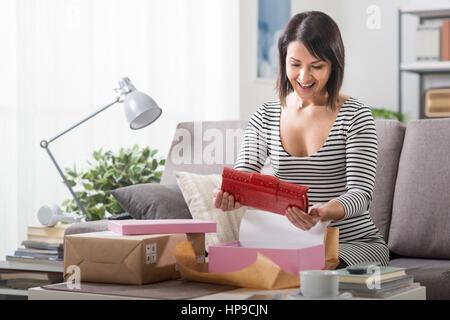 8f8aaacfc584 ... Donna felice unboxing un pacco contenente un sacco di moda, shopping  online con tempi di