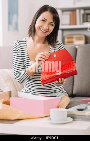 a9fdd88babc5 ... Sorridenti donna ricevere a casa una confezione regalo con un elegante  borsa di moda, shopping