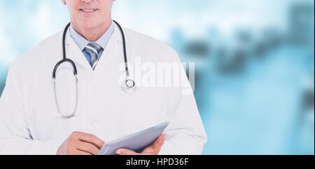 Medico sorridente guardando la fotocamera e tenendo compressa contro una apparecchiatura dentale Foto Stock