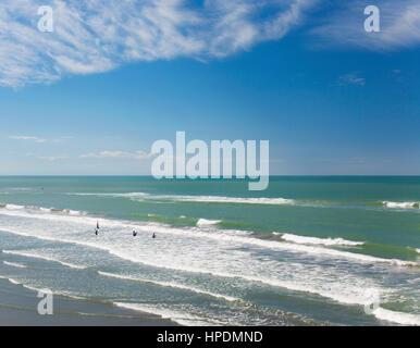 Christchurch, Canterbury, Nuova Zelanda. Vista sull'Oceano Pacifico off New Brighton Beach, giovani bodyboarders Foto Stock