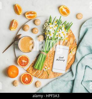 Tazza di caffè del mattino, i cookie, le arance rosse e la benna di fiori di primavera e il telefono cellulare con Foto Stock