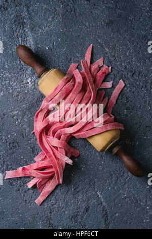 Crudo fresco non cotti in casa rosa barbabietola tagliatelle di pasta di legno sul perno di rotolamento su dark texture di sfondo di calcestruzzo. Vista da sopra con lo spazio.
