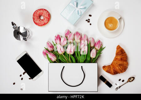 Vista dall'alto di fiori di primavera, caffè, telefono cellulare, croissant, dono e cosmetici. Piano immagine di Foto Stock