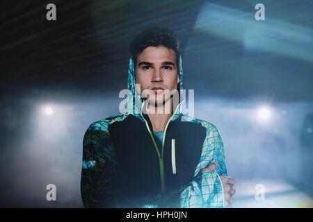 Ritratto di guida urbana permanente sulla strada di notte. Giovane uomo in abbigliamento sportivo in piedi sotto il ponte. Foto Stock