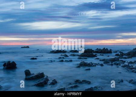 Kaikoura, Canterbury, Nuova Zelanda. Vista attraverso l'Oceano Pacifico da costa rocciosa all'alba. Foto Stock