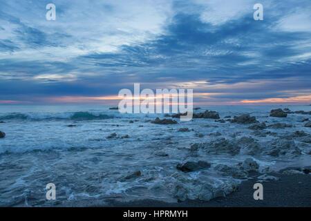 Kaikoura, Canterbury, Nuova Zelanda. Vista attraverso l'Oceano Pacifico da costa rocciosa di sunrise. Foto Stock