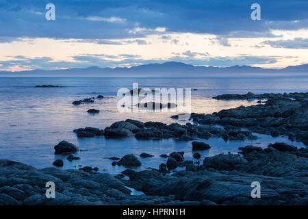 Kaikoura, Canterbury, Nuova Zelanda. Vista su tutta la baia a sud dalla spiaggia rocciosa al crepuscolo. Foto Stock