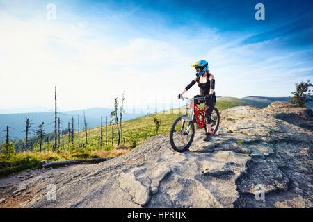 Femmina di MTB mountain biker si gode della vista durante la giornata di sole in montagna Foto Stock