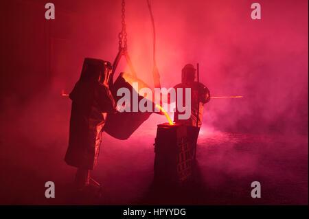 Colata di ferro fuso in un mulino di acciaio, la rievocazione dei lavoratori del settore metallurgico con benna Foto Stock