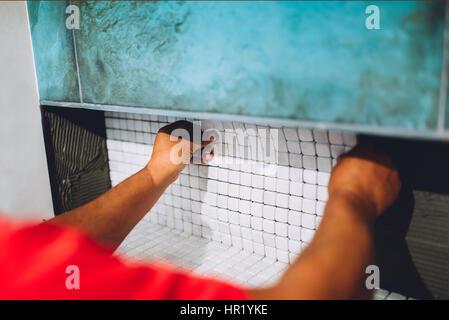 Lavoratore applicando adesivo piastrelle sul pavimento foto