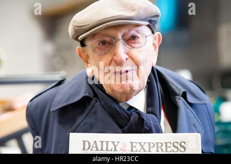 Ritratto di un panno cappuccio bianco che indossa il vecchio uomo con in mano una copia del Daily Express, un pensionato Foto Stock