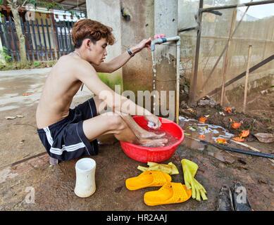 Giovane uomo pulizia , lavando i piedi, dopo di piantare le piantine di pomodoro in tunnel. Foto Stock