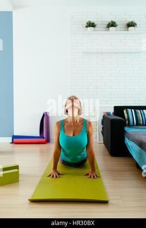 Donna di atletica a praticare yoga su un tappeto verde indoor. foto verticale Foto Stock