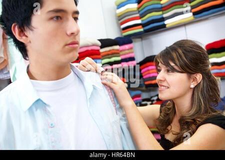 Sarto di prendere alcune misure di un uomo che è acquistare vestiti Foto Stock