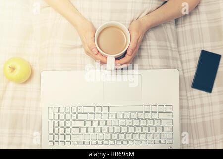 Lazy domenica - donna a bere caffè e utilizzando computer portatile a letto Foto Stock