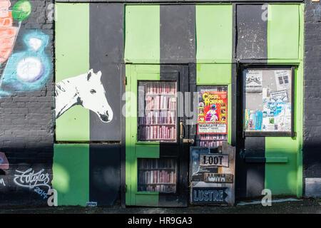 Un colorato negozio di fronte dipinta in verde e strisce nere sabbia spruzzati con graffiti in città vecchia a Margate, Foto Stock