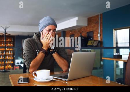 Preoccupato shoked uomo alla ricerca di un portatile presso il cafe Foto Stock