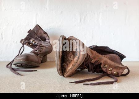 Coppia di usurati stivali vecchi, uno scarpone con la suola