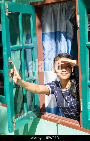 Donna felice guardando attraverso la finestra e si copre la faccia da sun. Una giovane donna guarda fuori dalla Foto Stock