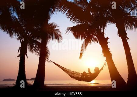 Donna relax in amaca sulla bellissima spiaggia del tramonto, concetto di vacanza Foto Stock