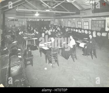Scrittura esame classe, Strada della Regina sera Institute, Londra, 1908. Artista: sconosciuto. Foto Stock