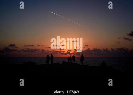 Magico tramonto su una spiaggia dell'isola di Gozo, Malta. L'immagine cattura la silhouette di viaggiatori che arrivano Foto Stock