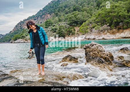 Attraente modello di moda ragazza in piedi sulla roccia bagnata a piedi nudi, tenendo scarponcini da trekking