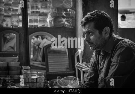 Un uomo perduto nel pensiero mentre è seduto alla sua bottega a Jaipur, India. Foto Stock
