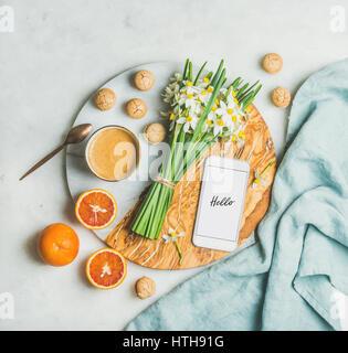 Caffè, biscotti, arance, fiori e il telefono cellulare con la parola Hello Foto Stock
