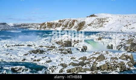 Una cascata ghiacciata in Islanda con cielo blu sulla giornata invernale Foto Stock